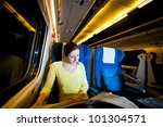 Young woman traveling by train at night - stock photo