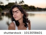 at sunset  a beautiful brunette ... | Shutterstock . vector #1013058601