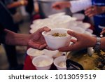 feeding the poor to hands of a... | Shutterstock . vector #1013059519