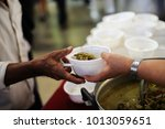 feeding the poor to hands of a... | Shutterstock . vector #1013059651