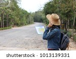 a backpacking woman holds map... | Shutterstock . vector #1013139331