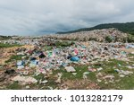 the huge waste pile extends... | Shutterstock . vector #1013282179