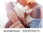 Stock photo  black and white cat licks the nose of a young beautiful woman in a white sweater 1013376271