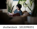 young happy asian woman reading ... | Shutterstock . vector #1013398351
