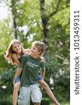 girl riding on boy's back | Shutterstock . vector #1013459311