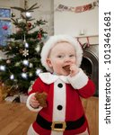 a baby dressed as santa eating... | Shutterstock . vector #1013461681