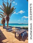 Small photo of Tables and chairs in a cafe with palm trees on the beach Lara, Cyprus