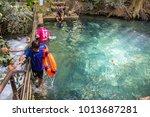 people playing near waterfall ... | Shutterstock . vector #1013687281
