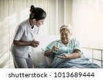nurse giving senior woman... | Shutterstock . vector #1013689444