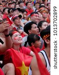 Small photo of HO CHI MINH CITY, VIET NAM- JAN 27, 2018: Portrait of Vietnamese football fans sit and watch AFC U23 soccer final match from outdoor Tv screen at Nguyen Hue walking street, amazing with red flag