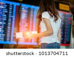 Small photo of girl in international airport with passport and boarding pass near flight information board