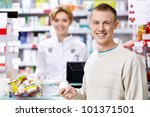 The pharmacist and the customer at the counter - stock photo