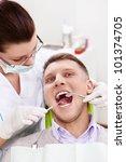 Dentist treats teeth of patient - stock photo