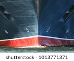 Ship Bow from dead ahead with anchors and bow wave. Ship is black and red hull showing anchors on port and starboard sides - stock photo