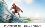 Young Surfer Rides Ocean Wave...
