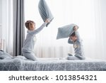 Stock photo naughty children little boy and girl staged a pillow fight on the bed in the bedroom they like 1013854321
