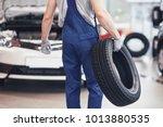 mechanic holding a tire tire at ...   Shutterstock . vector #1013880535