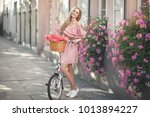 Stock photo pretty young woman is riding on a white bicycle in the city she is smiling and wearing a pink off 1013894227