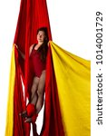 Small photo of Beautiful aerialist girl doing acrobatic and flexible tricks on red aerial silks (tissues) isolated on white background