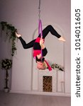 Small photo of Beautiful aerialist girl doing acrobatic and flexible tricks on aerial ring (lyra) in photostudio with falseness arch and decorations on white wall