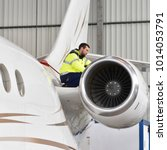 Stock photo airport workers check an aircraft for safety in a hangar 1014053791