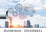 Small photo of Businessman in helmet drawing sketches of gear mechanism while standing on broken bridge with cityscape and sunlight on background. 3D rendering.
