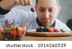 chef man put cherry to the cake ... | Shutterstock . vector #1014260539