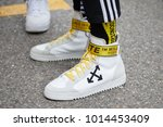 Small photo of MILAN - JANUARY 15: Man with Off White sneakers with yellow belt before Represent fashion show, Milan Fashion Week street style on January 15, 2018 in Milan.
