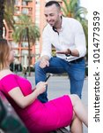 Small photo of Young male is acquaintance with girl who is sitting on bench in the park.