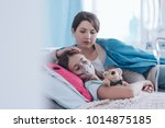 worried mother taking care of a ... | Shutterstock . vector #1014875185