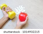 hands hold dumbbell and red... | Shutterstock . vector #1014932215