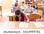 children taking an exam | Shutterstock . vector #1014999781