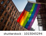 Small photo of American flag with stars and gay pride rainbow stripes hanging from traditional Brooklyn building in the liberal city of New York