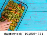 Small photo of Chef serving a dish of fresh roast vegetables placing a small baby potato in place on green asparagus, tomato and bell peppers with a pair of tongs close up overhead view with copy space