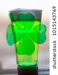 Small photo of A plastic glass with beer, green with abundant foam with clover emblem . Close-up