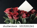Small photo of A bunch of red roses in an upright grouping with blank white message card at eye level. Black background.