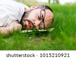 Small photo of weary man relaxing outdoors lying on the grass with a book