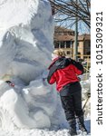 Small photo of LAKE GENEVA, WI/USA - FEBRUARY 1, 2018: A sculptor uses a fork-shaped tool to modify a notch in a tall block of snow at the U.S. National Snow Sculpting Competition during a winter festival.