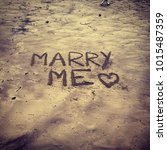 marry me written in the sand on ... | Shutterstock . vector #1015487359