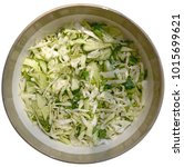 Small photo of Top close-up isolated view of fresh spring salad oaf sliced cabbage with cucumber, green onion and dill t is in round ceramic bowl.