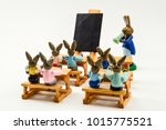 Small photo of Toy rabbits arranged to mimic a classroom full of students and a teacher complete with desk and writing boards. These toys were bought in thrift store and arrange in a light box.