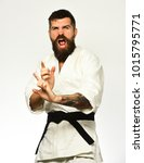 Small photo of Man with beard in white kimono on white background. Karate man with mad excited face in uniform. Healthy lifestyle and sports concept. Aikido master with black belt practices attack or defense posture
