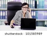 Happy asian businesswoman talking on the phone in the office - stock photo