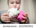 a baby holding piggy banks | Shutterstock . vector #1015902901