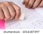 Stock photo hand with white ruber eraser on white paper mistake erase concept 1016187397
