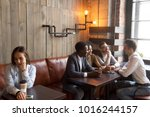 Small photo of Diverse multiracial people hanging together in coffeehouse ignoring sad young girl sitting alone at cafe table, upset social outcast loner suffers from unfair attitude or discrimination among friends