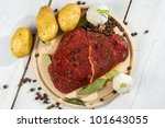 Raw steak spiced with herbs ready for baking - stock photo