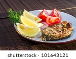 Fried fish served on a plate with vegetables - stock photo