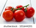 Fresh wet tomatoes on a old white plank - stock photo