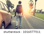 Small photo of A man parking his car on the road and carrying backpack to continue walking.